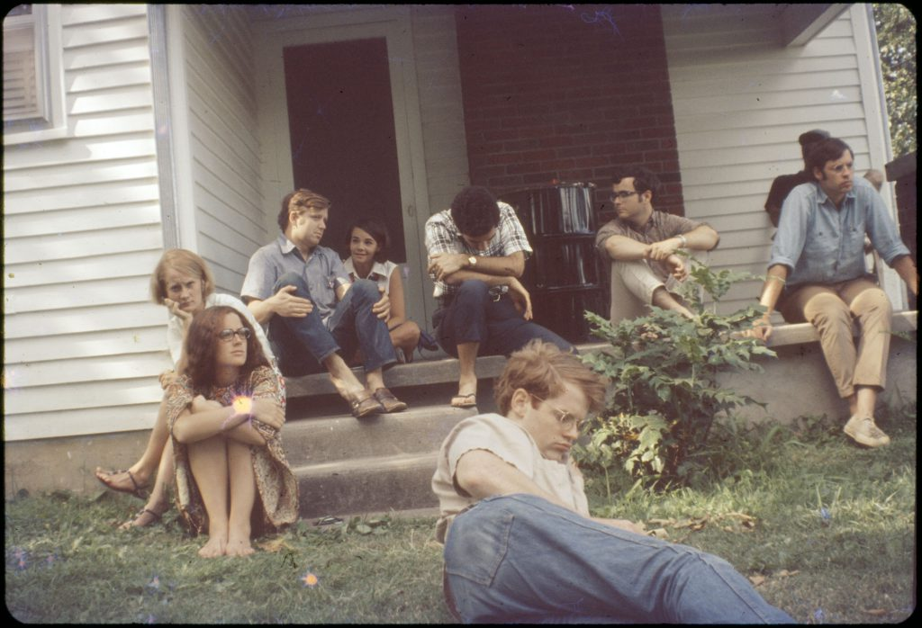 A group of students waiting for dinner. Includes Bill Dow in the foreground, Dr. Pete Moss sitting on the edge of the porch with light blue shirt and khaki pants. Others include Sara Graf, Margaret Ecker, Tod L'Hommedieu and Ron Massey. RD Slide 154