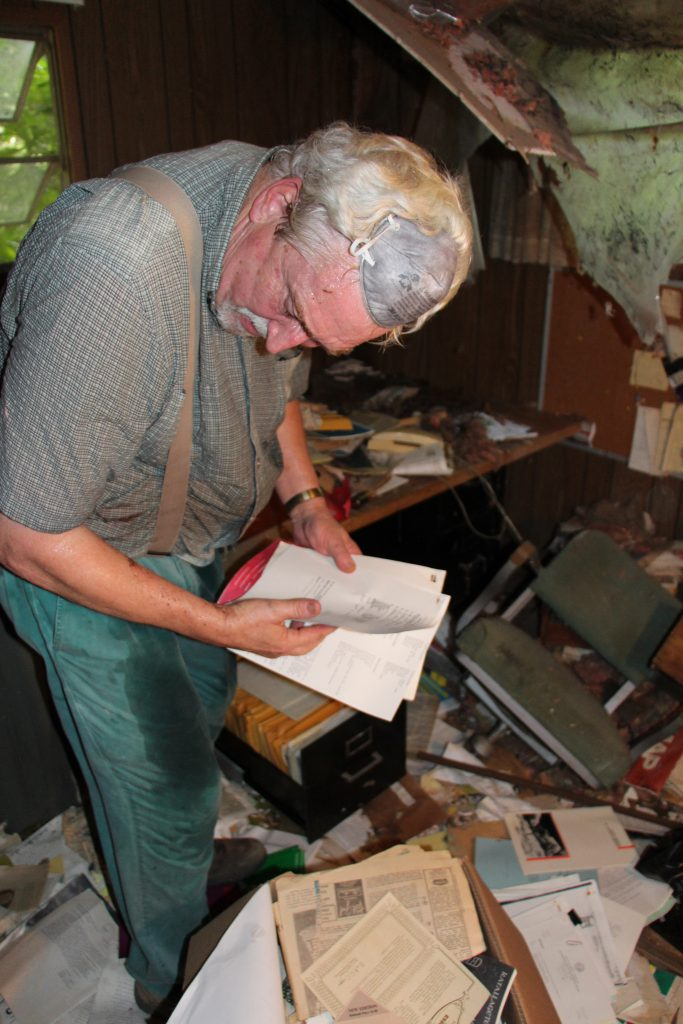 Tom John sorting through a stack of papers in Bill's farm trailer office