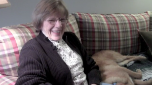 Martha Stucker is sitting with her dog, Luke, on a plaid couch in her Durham, NC living room. She has a smile on her face while recounting to the interviewer her first impressions of Bill Dow.
